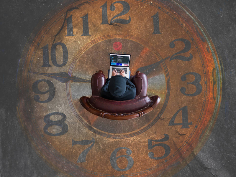 Developer with a laptop sitting on a chair inside of an analog clock on the ground